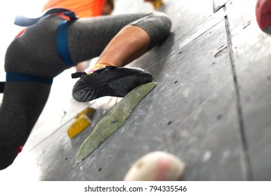 Climbing shoes in boulder climbing hall. Fitness, extreme sport, bouldering, people and healthy lifestyle concept - people exercising at indoor climbing gym. Close-up image