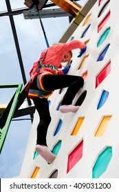 Climbing wall for children. The parkour Park, climbing wall and trampolines. The little girl on the climbing wall. Vacation, holiday.