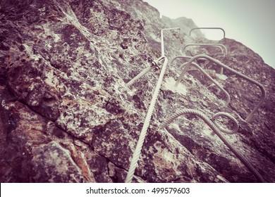 Climbing wall in Italy, Detail climb ferrata, Via ferrata in mountains in summer, Via ferrata in mountains, Symbol mountain climbing