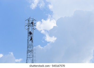 Climbing worker installing new telecommunication in high and danger tower  in blue sky