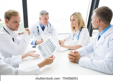 Clinic, people, healthcare and medicine concept - group of medics with brain x-ray scan at hospital