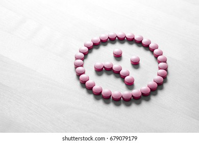 Clinical depression, mental illness and disorder or bad health services concept. Sad smiley face made from pills, medicine and tablets on wooden table. Dissatisfied and unhappy icon.
