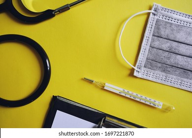 Clinical flat type thermometer, disposable medical masks with activated carbon filter, stethoscope and clipboard on yellow background. Coronavirus disease or COVID-19 theme. (space for text)