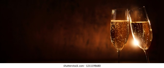 Clink glasses with champagne for the new year on festive dark background for a congratulations card