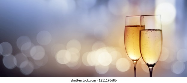 Clink glasses with champagne for a new year on abstract blue bokeh background