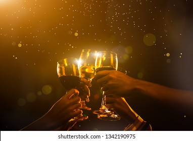 Clink Glasses at night party celebration friends group golden tone, Hands holding wine for event festival.