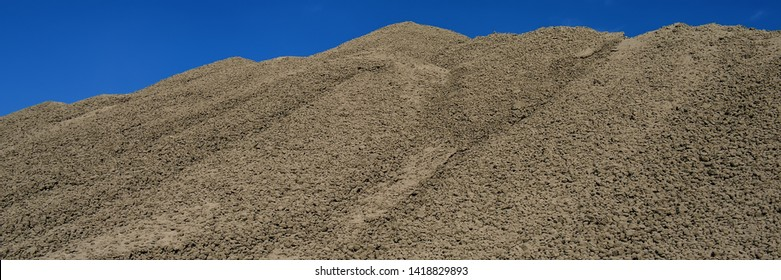 clinker surface in a raw material warehouse and blue sky, cement production. Web banner for your design.