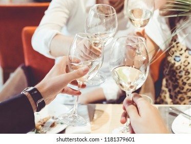 Clinking glasses above dinner table. Hands of people with glasses. Celebrating and toasting in honor of the wedding or other celebration.