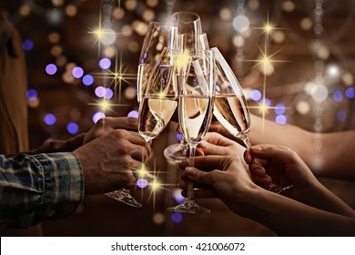 Clinking glasses of champagne in hands on bright lights background with snow effect