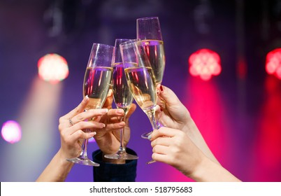 Clinking glasses of champagne in hands on bright lights background