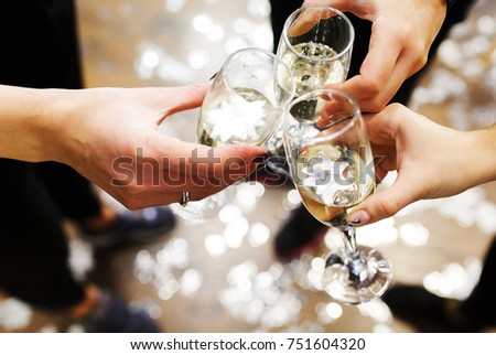 Clinking glasses with champagne in hands on bright confetti background, cheers, party