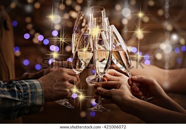 Zwirnende Gläser Champagner in Händen auf hellem Hintergrund mit Schneeeffekt