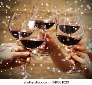Clinking glasses of red wine in hands on wooden background over snow effect