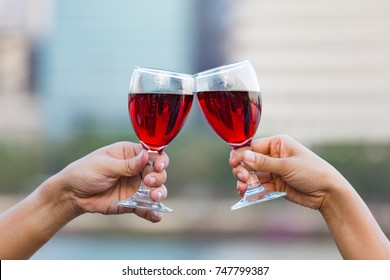 Clinking glasses of red wine in hands on nature lights background