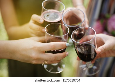 Clinking glasses with red wine and toasting. cheers glasses and party concept
