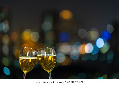 Clinking with two beer mug or glasses over the photo blurred of cityscape for celebrate, party and celebrate with happy new year concept