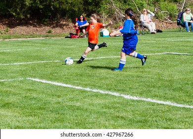 Clinton, CT, USA - May 21, 2016: Daytime scene of young girls playing soccer in an all girls team on May 21, 2016. The game is an organized youth soccer game.