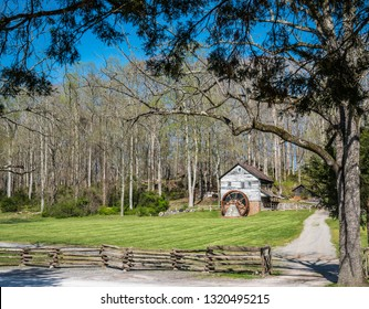 Clinton, TN / USA - April 12, 2019 - beautiful old grist mill standing behind the deciduous tree.  Fresh, bright green grass and deciduous trees add to the rural scenery.  Museum of the Appalachia