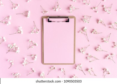 Clip board with paper mockup. Floral pattern made of white gypsophila on a pink punchy pastel background