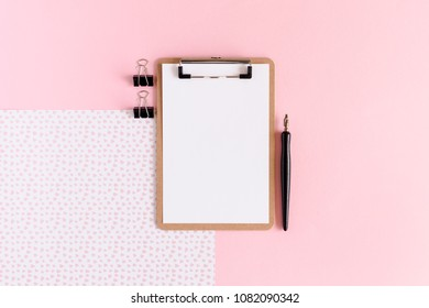 Clip board with white blank paper, black paper clips, calligraphic pen on a pink pastel background