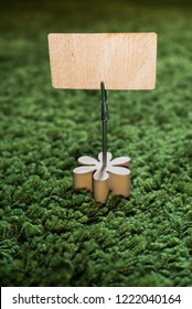 Clip card holder with wooden flower on green grass carpet holding a natural wooden announcement display with empty space for text and copy - Flowerpower holder with blank space to use as invitation