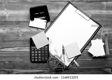 Clip folder with white paper near hole puncher, stickers, colorful elastics, paper clips and pen. Stationery and calculator on wooden background. Business supplies concept. Business cards, copy space