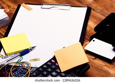 Clip folder with white paper near hole puncher, stickers, colorful elastics, paper clips and pen. Business cards, copy space. Stationery and calculator on wooden background. Business idea concept.