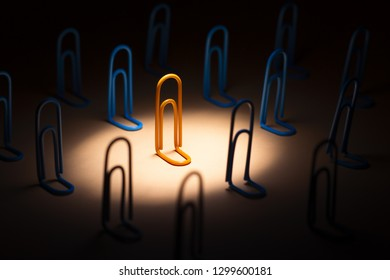 clip highlighted by the spotlight from above among crowd, the moral: a person chooses of life and the mood of an optimist or pessimist, a creative idea of the concept of success and glory