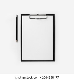 Clipboard with blank letterhead and pencil on white paper background. Top view. Flat lay.