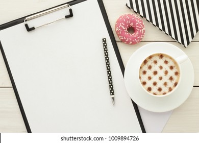Clipboard with blank paper, cup of coffee with cinnamon and donuts on white wooden desk table. Coffee break, home office desk, ideas, notes, plan writing or sketching  concept. Top view, flat lay.