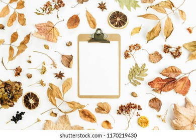 Clipboard with blank paper on dry fall autumn leaves background. Flat lay, top view.