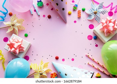 Clipboard and colorful decorations on pink pastel background. Flat lay, top view. Birthday background, holiday concept.