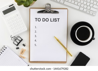 Clipboard with to do list words on office table with keyboard, coffee, stationery, box file and smartphone.