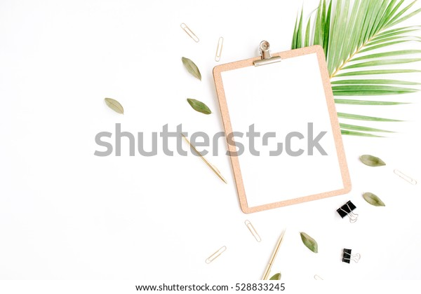 clipboard with empty copy space blank, golden pen and clips, petals and palm branch on white background. flat lay, top view
