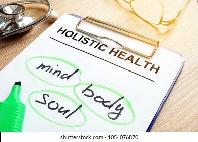 Clipboard with Holistic health and words mind, body and soul.