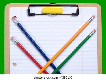 Clipboard with notebook paper, pencils and erasers arranged to provide copy space on paper.