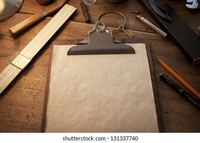 Clipboard and old parchment like blank paper under incandescent light, with vintage feeling.
