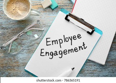 Clipboard and paper with text EMPLOYEE ENGAGEMENT on wooden table