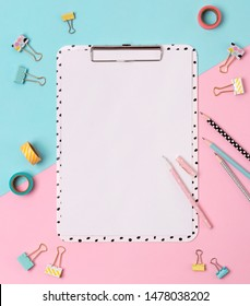 Clipboard, pen, binder,  pencil and duct tape at creative pink and blue background. Workspace mockup. Flat lay, top view