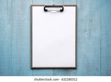 Clipboard with white paper on wood background. Top view. Mock up for word.