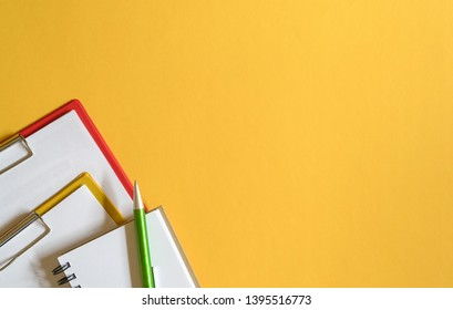 Clipboards, memo pad and green pen on yellow top or desk background. Copy Space