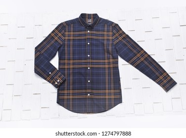 clipping path, top view of folded yellow and blue color long sleeve plaid shirt isolated