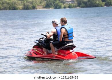 CLITHERALL, MINNESOTA / USA - JULY 17, 2016: Two teenage boys wearing life vests driving Sea-Doo personal watercraft PWC on the lake.