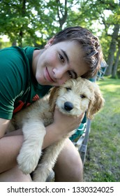 CLITHERALL, MINNESOTA / USA - MAY 29, 2016: Happy young teen boy embracing Odin his new Goldendoodle puppy.