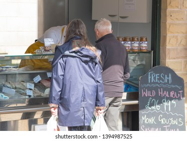 Clitheroe, Lancashire/UK - May 11th 2019: caucasian middle age man and woman shopping at a fishmongers shop in a town market on a sunny Saturday afternoon