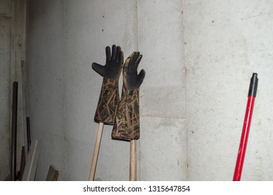 Cllutter in the basement includes a pair of elbow length trappers gloves.