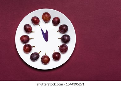 Clock of 12 piece grapes on red background. New Year concept. Spanish tradition for the new year.