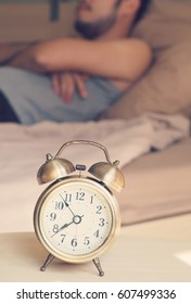 Clock alarm with de-focus a man background.