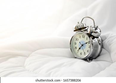 Clock alarm on bed in bedroom  in the morning.