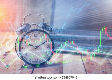 Clock alarm with stock graph chart in laptop screen background.Time,stock market,business success and investment concept.
